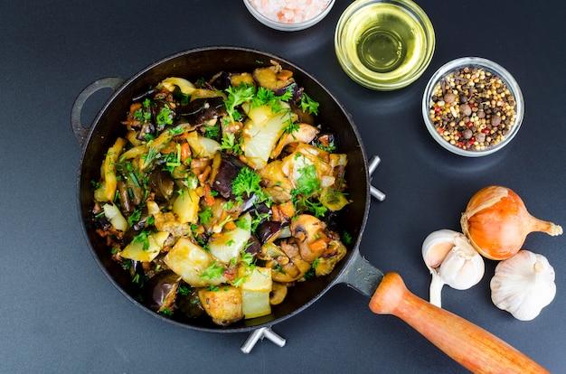 Aubergines frites, paprika et différents légumes dans une casserole sur fond noir Photo Premium