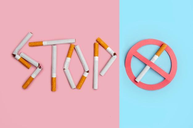 Aucun signe de fumer. le mot stop orthographié à l'aide de cigarettes cassées sur fond coloré. Photo Premium
