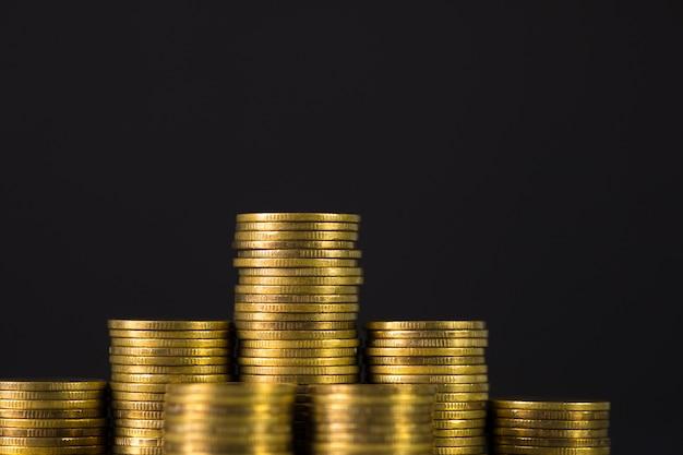 Augmentation des colonnes de pièces, étape des piles pièce sur fond sombre avec espace de copie pour les entreprises et le concept financier. Photo Premium