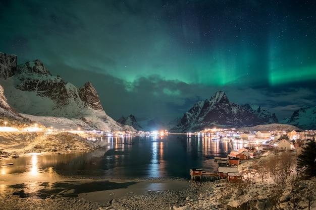 Aurore boréale au-dessus de la lumière d'un village scandinave qui brille en hiver Photo Premium