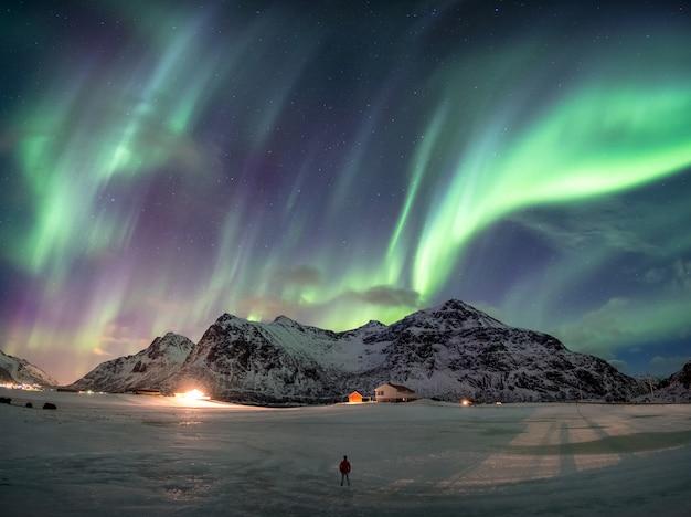 Aurore boréale fantastique sur montagne enneigée avec homme debout Photo Premium