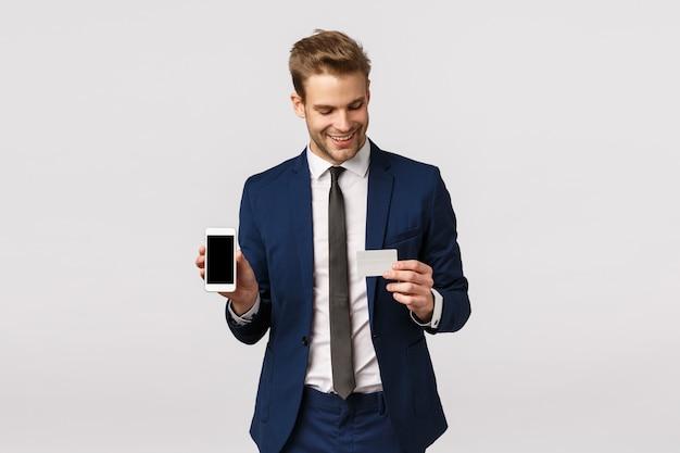 Auto-assuré Jeune Homme D'affaires Blond En Costume Classique Bleu, Tenant Un Smartphone Et Une Carte De Crédit, Montrant Un Affichage Mobile, Un Mode De Paiement En Ligne, Une Application Financière, Debout Sur Fond Blanc Photo Premium