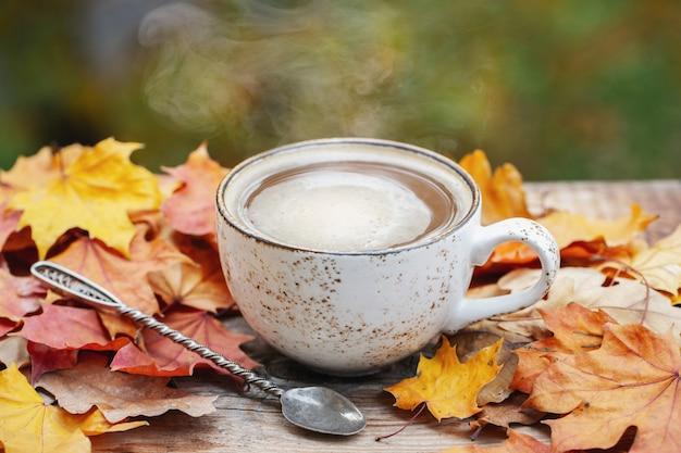 Automne, feuilles d'automne, tasse de café chaude et fumante. Photo Premium