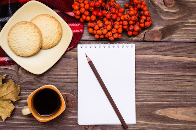 Automne nature morte café, biscuits, un plaid, un cahier et un crayon sur bois Photo Premium
