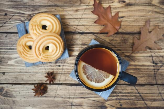 Automne nature morte avec une tasse de thé, des biscuits, un pull et des feuilles sur une surface en bois. Photo Premium