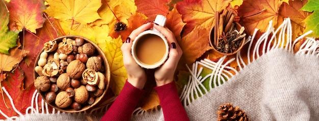 Automne plat poser. mains féminines avec une tasse de café, plaid beige, bol en bois avec noix Photo Premium