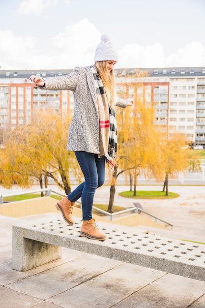 Automne vêtu femme équilibre banc de pierre Photo gratuit
