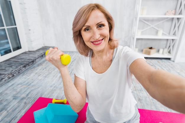 Autoportrait d'une belle femme exerçant avec des haltères Photo gratuit