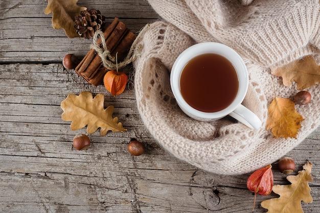 Autumn flat poser sur une table en bois avec une tasse de thé et de feuilles jaunes tombées sèches. Photo Premium