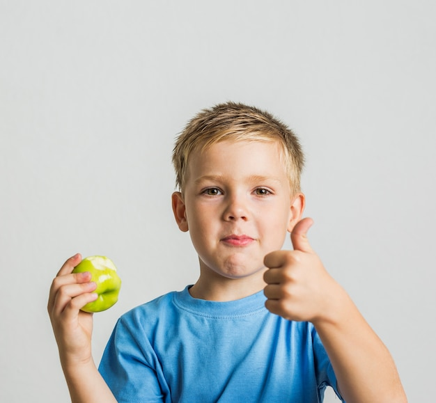 Avant jeune garçon avec une pomme verte Photo gratuit