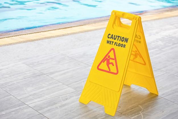 Avertissement plaques humide sol au bord de la piscine. Photo Premium
