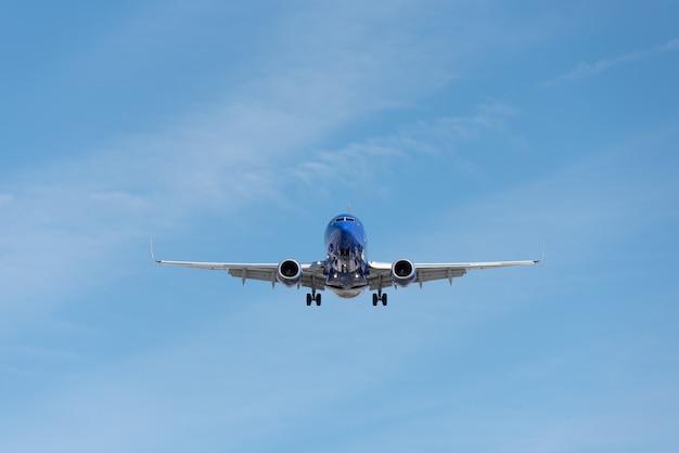 Avion commercial volant dans le ciel bleu, volet complet et train d'atterrissage sorti Photo Premium