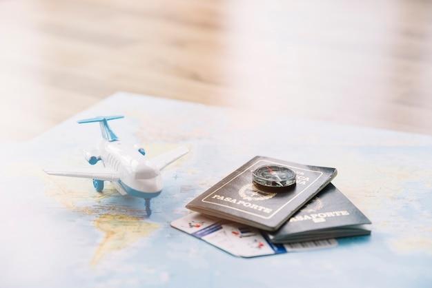 Avion jouet blanc; boussole sur les passeports et carte de bagages sur la carte contre la table en bois Photo gratuit