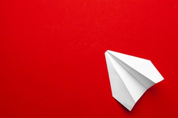 Avion en papier blanc sur fond rouge Photo Premium
