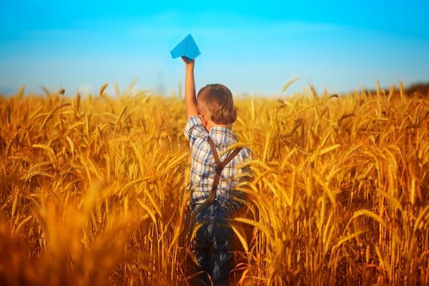 Avion en papier bleu dans les mains des enfants sur le champ de blé jaune et ciel bleu en jour d'été Photo Premium