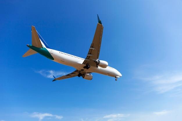 Avion de passagers d'atterrissage clair fond bleu de ciel et nuages Photo Premium