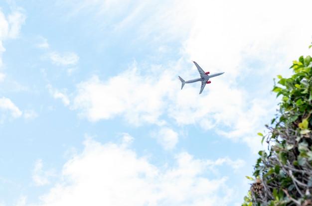 Avion volant à basse altitude dans un ciel nuageux et dégagé Photo Premium