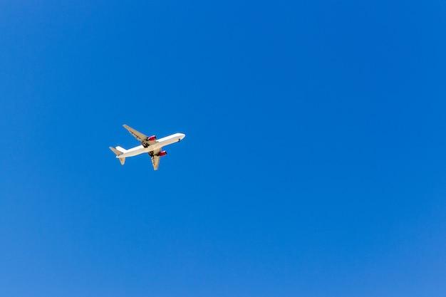 Un avion volant dans le ciel bleu sans nuages blancs Photo Premium