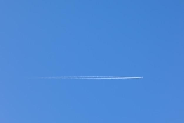 Avion volant à travers le ciel bleu clair, avec un sentier derrière. Photo Premium
