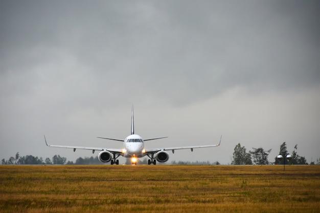 Les avions de passagers avec des lumières allumées se rendront sur la piste du terrain de l'aéroport le soir sous la pluie Photo Premium