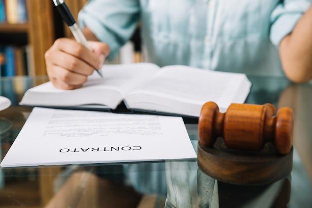 Avocat assis avec maillet, contrat et livre à table Photo gratuit