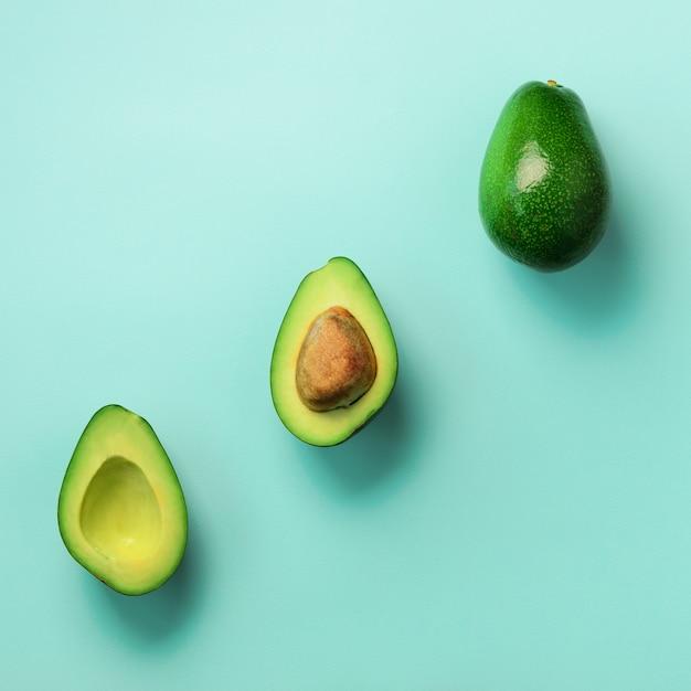 Avocat Bio Aux Graines, Moitiés D'avocat Et Fruits Entiers Sur Fond Bleu. Modèle D'avocat Vert Dans Un Style Plat Minimal. Photo Premium
