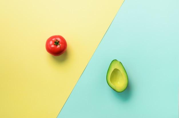 Avocat Bio, Tomate Sur Fond Bleu Et Jaune. Motif De Légumes Dans Un Style Plat Minimal. Photo Premium