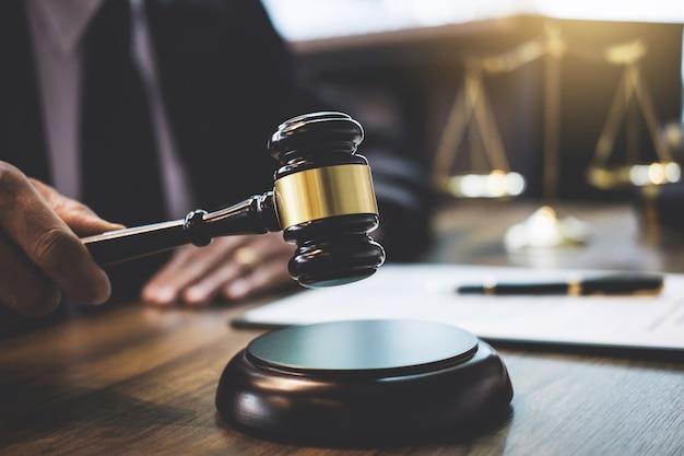 Avocat ou conseiller travaillant sur un document et tenant un marteau dans la salle d'audience, la justice et le droit Photo Premium