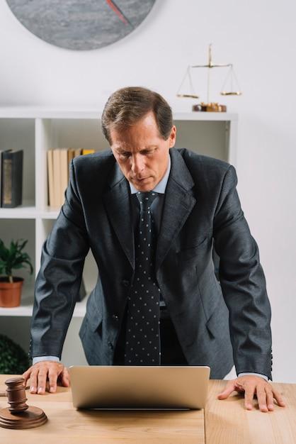 Avocat homme mûr regardant un ordinateur portable sur le bureau Photo gratuit