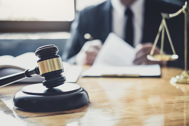 Avocat ou juge travaillant avec des documents contractuels, des livres de droit et un marteau en bois sur une table dans une salle d'audience, avocats de la justice dans un cabinet d'avocats, concept de services juridiques Photo Premium