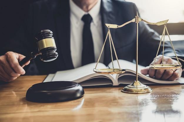 Avocat Ou Juge Travaillant Avec Des Documents Contractuels, Des Livres De Droit Et Un Marteau En Bois Sur Une Table Photo Premium