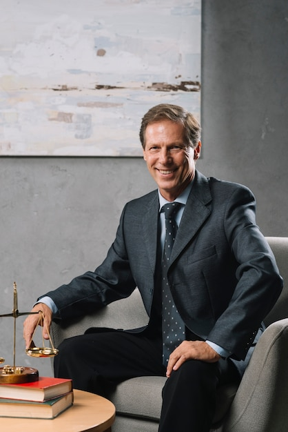 Avocat mature homme confiant assis dans le bureau Photo gratuit