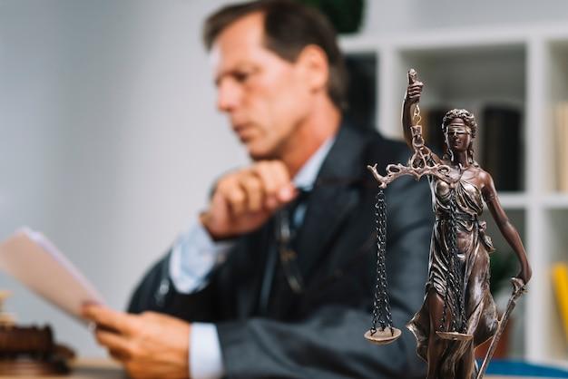 Avocat professionnel lecture document avec justice statue à l'avant Photo gratuit