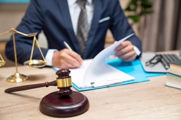 Avocat travaillant avec des papiers de contrat et marteau en bois sur table dans la salle d'audience. Photo Premium