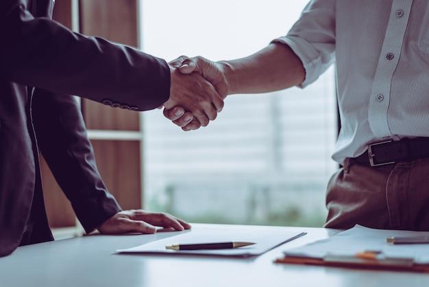 Des avocats d'avocats asiatiques partenaires d'âge moyen se serrant la main après avoir discuté d'un contrat. Photo Premium