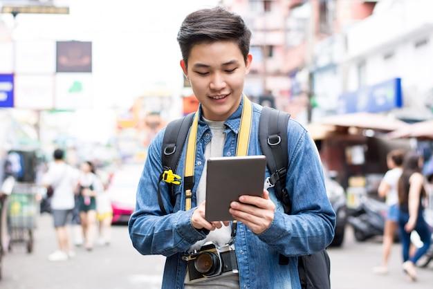 Backpacker de touristes asiatiques à l'aide d'une tablette lors d'un voyage à khao san road thailand Photo Premium