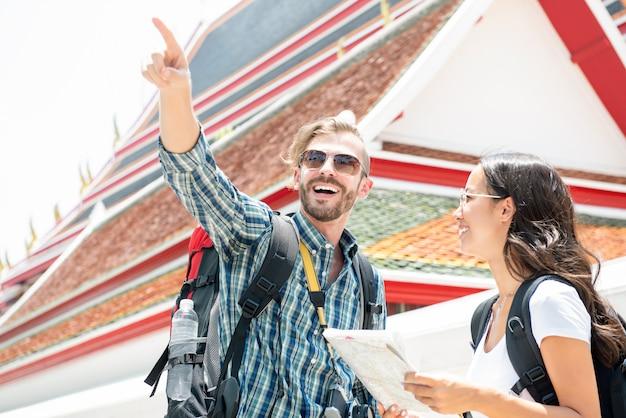 Backpackers touristiques voyageant dans l'ancien temple thaïlandais en vacances en thaïlande Photo Premium