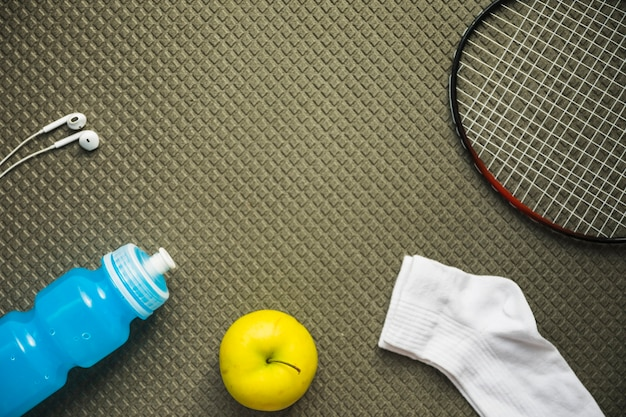 Badminton; pomme; chaussette; bouteille d'eau et écouteurs sur fond texturé Photo gratuit