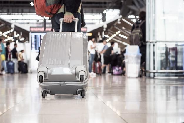 Bagages de voyage à pied au terminal de l'aéroport pour l'enregistrement. Photo Premium