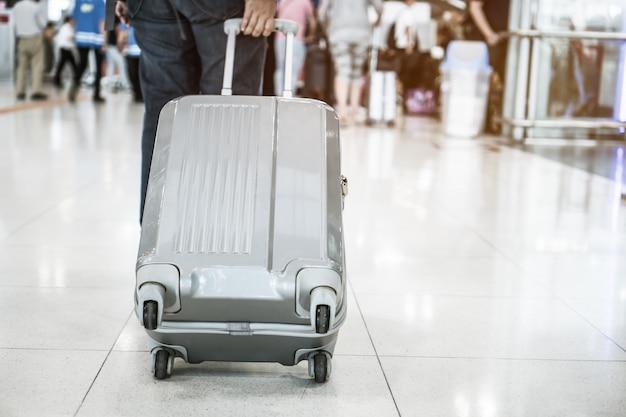 Bagages de voyage à pied au terminal de l'aéroport pour l'enregistrement Photo Premium