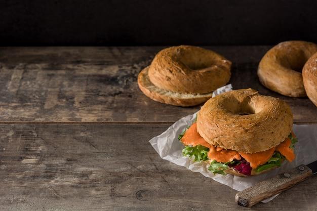 Bagel avec du fromage à la crème, du saumon fumé et des légumes sur une table en bois espace de copie Photo Premium