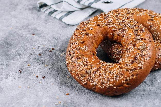 Bagel de grains entiers biologiques sains sur la table de fond en béton Photo Premium