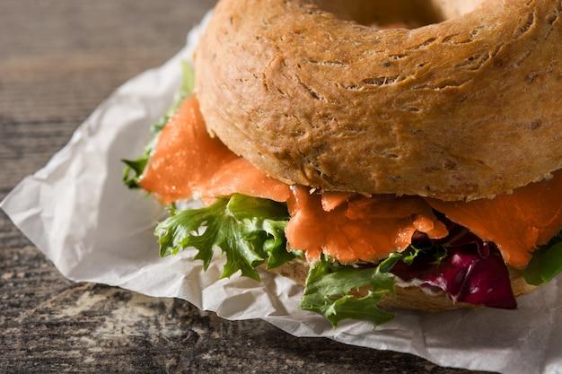 Bagel sandwich au fromage à la crème, saumon fumé et légumes sur la table en bois se bouchent Photo Premium