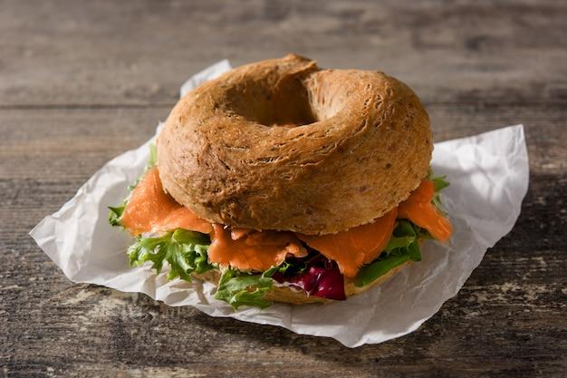 Bagel sandwich au fromage à la crème, saumon fumé et légumes sur une table en bois Photo Premium