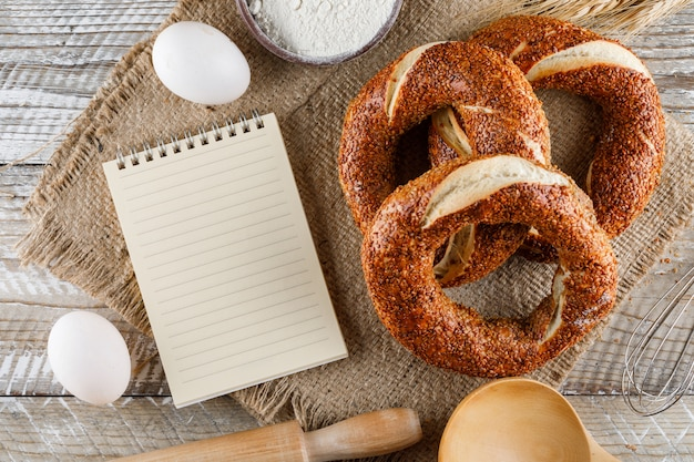 Bagel Turc Avec Bloc-notes, Oeufs, Rouleau à Pâtisserie Vue De Dessus Sur Un Tissu De Sac Et Surface En Bois Photo gratuit