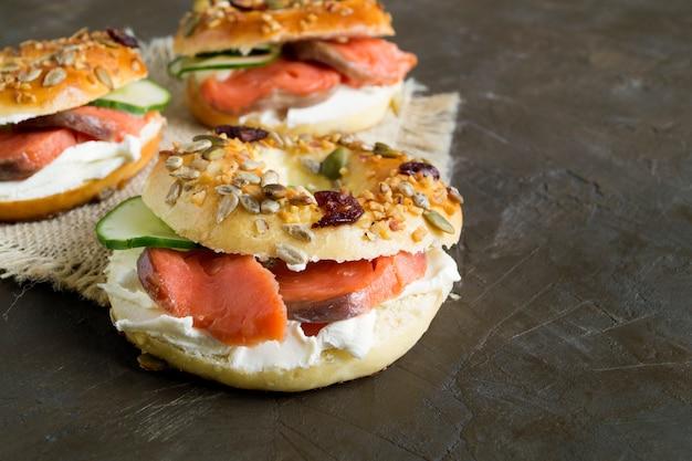 Bagels au fromage à la crème et au saumon fumé sur fond noir Photo Premium