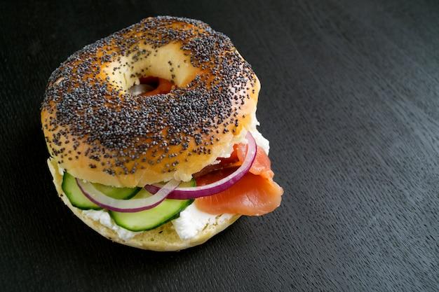 Bagels au fromage à la crème et saumon fumé sur fond noir Photo Premium
