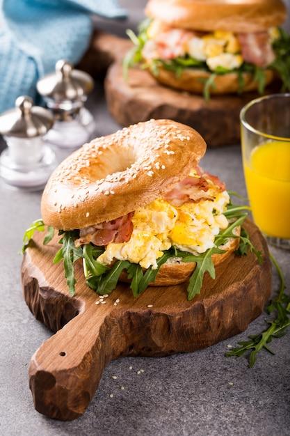 Bagels aux oeufs brouillés, rucola et bacon frit Photo Premium