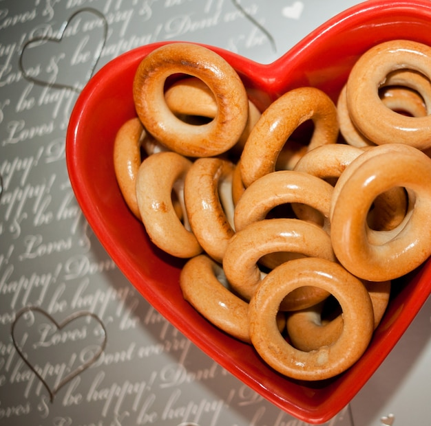 Bagels sur plaque rouge en forme de coeur sur gris. Photo Premium