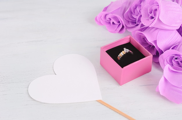 Bague à diamants dorés dans une boîte rose avec bouquet de roses roses Photo Premium